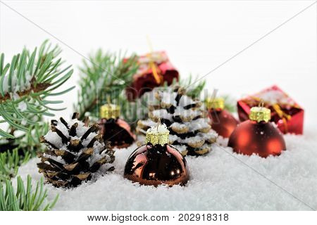 An Image of a Christmas deco with balls, snow,and tree
