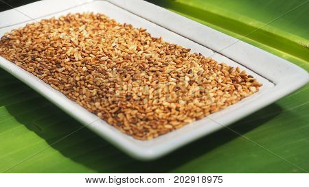 White sesame seed roasted in ceramic white color on banana leaf background and extra close up macro photo focus select at center of picture.