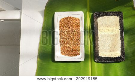 Background white sesame and roasted modern art style in ceramic plate on banana leaf green color design on white chair and floor in kitchen with sun lighting has copy space.