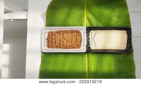Background white sesame and roasted modern art composition in ceramic plate on banana leaf green color design on white chair and floor in kitchen with sun lighting has copy space.