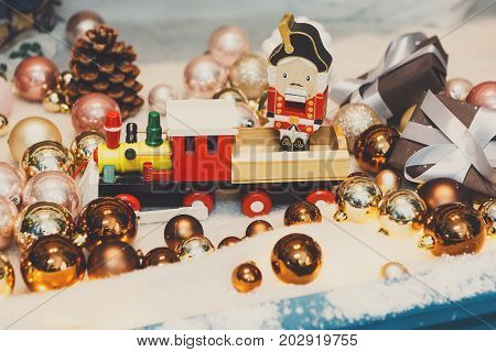 Christmas gifts background. Vintage wooden toy train and nutcracker on snow with golden shiny baubles and small present boxes. Magical atmosphere of new year eve, closeup
