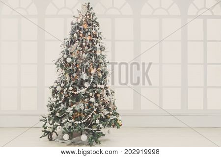 Christmas magic background. Beautiful decorated xmas tree in white living room. Shining lights, balls, baubles and garland. Winter holidays magic atmosphere. Modern design and decorations, copy space