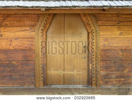 Ancient antique wooden doors of the old hut with wrought iron crossbar.