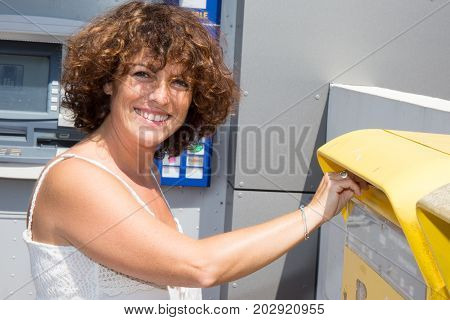 Woman Posting Letters Inserting Into A Postal Mailbox