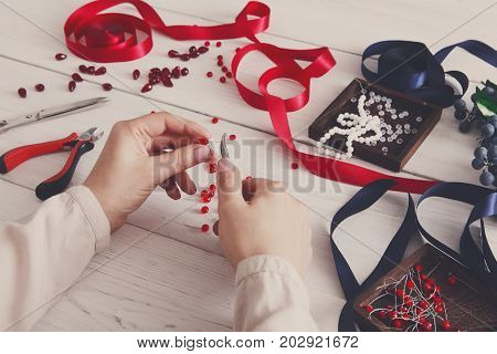 Woman making jewelry, home workshop. Artisan pov, female hands creating accessory with beads and ribbons, filtered image. Beauty, creativity, handicraft concept