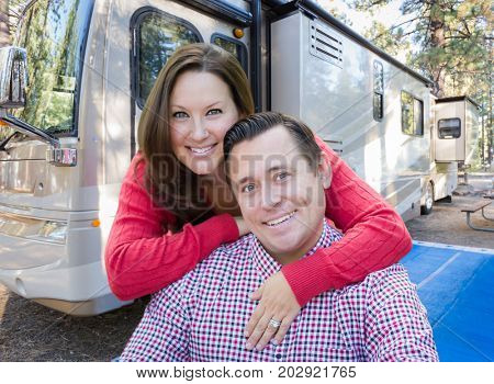 Happy Caucasian Couple In Front of Their Beautiful RV At The Campground.