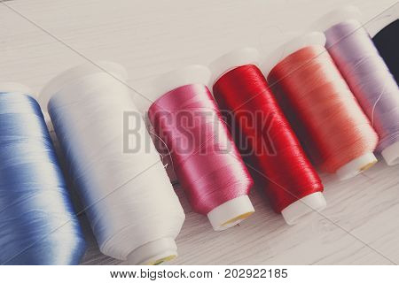 Colorful thread spools on wooden table close up. Sewing string, filtered image. Art, handicraft concept