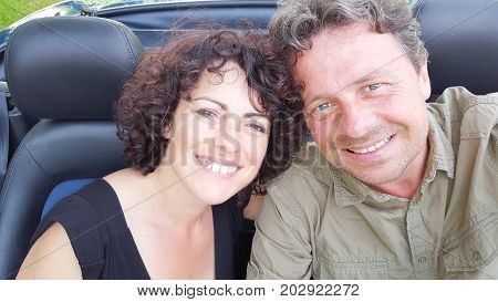 A Middle-aged Couple Snuggle Together As They Zoom Down A County Road In A Classic Convertible Car