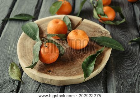 Macro photo of a cutted mandarin with green leaves on a black wooden table. Tasty tangerines for the New Year festive table