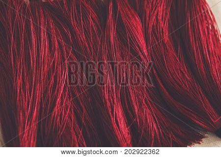 Red tassels background close up. Woman handicraft, filtered image. Art, creativity, hobby, home workshop concept
