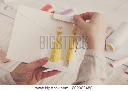 Handmade earrings packing, home workshop. Woman artisan put tassel jewelryinto original boxes, top view, filtered image. Art, hobby, handicraft concept