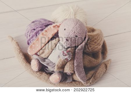 Cute handmade rabbit with wool close up. Plush vintage toy with materials of it, copy space, filtered image. Creativity, handicraft, hobby concept