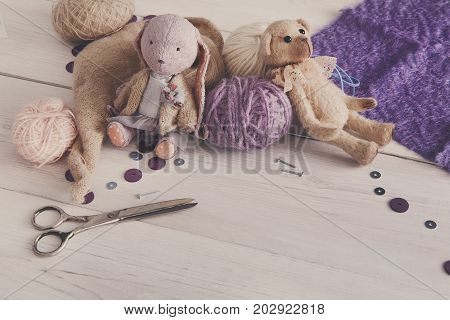 Handmade toy making, artisan workplace. Bear and rabbit with materials for creating vintage plaything, home workshop, copy space for text, filtered image