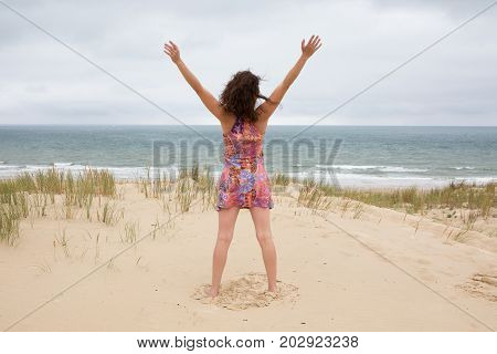 Attractive Middle Aged Woman Standing In The Ocean With Her Arms Held Up