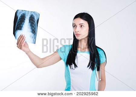 Female doctor or nurse looking at radiography photo.