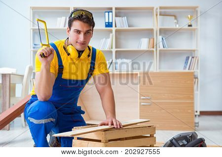 Repairman carpenter working sawing a wooden board with a hand sa