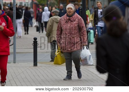 KAZAN, RUSSIA - September 5, 2017: tired adult woman on street with shopping bags, telephoto shot