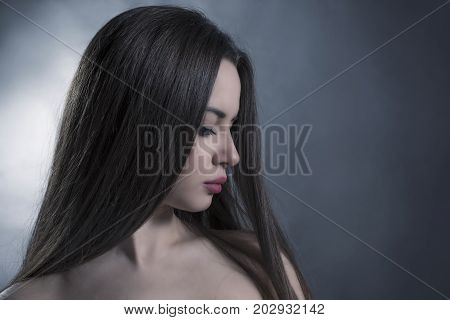 Side view glamour woman portrait with long hair over grey background