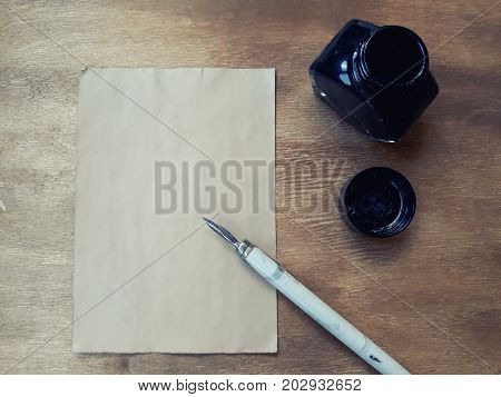 Blank old sheet of paper with a dip pen and an inkwell on a worn wooden background (view from the top or flat lay) retro style