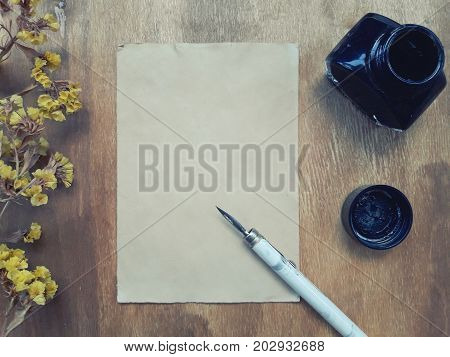 Dry autumn flowers and a blank old sheet of paper with a dip pen and an inkwell on a worn wooden background (view from the top or flat lay) retro style
