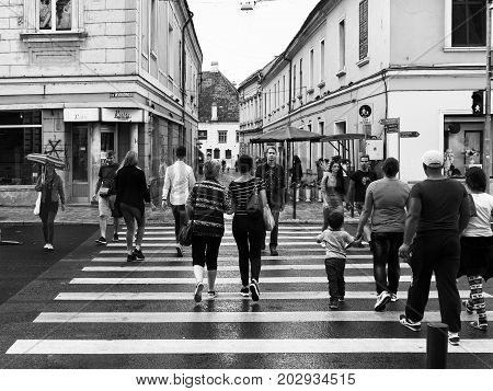 CLUJ-NAPOCA ROMANIA - SEPTEMBER 2 2017: People crossing the street at the pedestrian crossing on a rainy day in downtown Cluj-Napoaca. Black & white