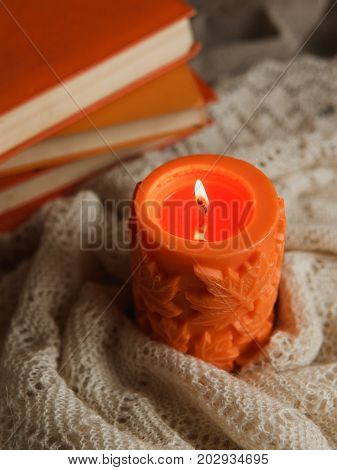 Autumn Cozy Still Life Of Big Orange Candle And Pile Of Books With Warm Scurf.