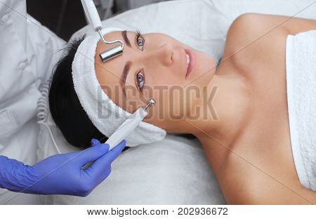 The cosmetologist makes the apparatus a procedure of Microcurrent therapy of a beautiful young woman in a beauty salon. Cosmetology and professional skin care.