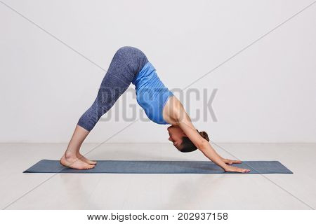 Woman doing Ashtanga Vinyasa yoga Surya Namaskar Sun Salutation asana Adhomukha svanasana - downward facing dog on yoga mat in studio on grey bagckground