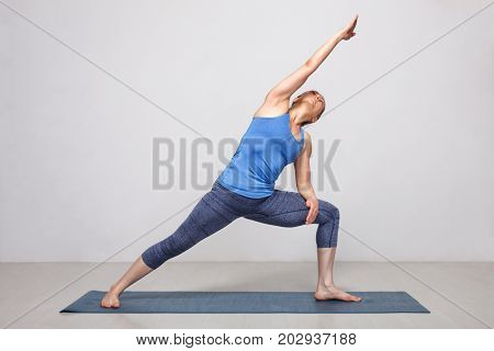 Woman doing Ashtanga Vinyasa yoga asana Utthita parsvakonasana - extended side angle pose beginner variation on yoga mat on yoga mat in studio on grey bagckground