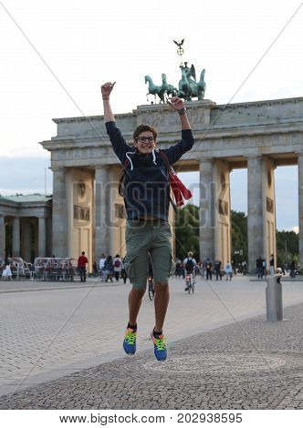 young caucasian boy makes a big leap in the Berlin square in front of the Brandenburg Gate