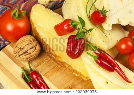 Sliced hard cheese on the kitchen board. Production of cheeses on the farm. Spicy cheese tomatoes garlic chilli pepper