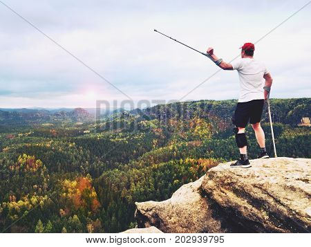 Hiker With Knee Joint Bandage And Forearm Poles. Hiker On Cliff Makes Triumph Gesture.