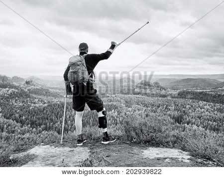 Disabled Man On Crutches On Rock. Hurt Knee In Neoprene Metal Knee Braces And Man Hold Forearms Crut