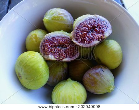 Fresh fig in a bowl. Many figs in a bowl. One fig is cut open in half. Open fig is rip and juicy, perfect purple colour.