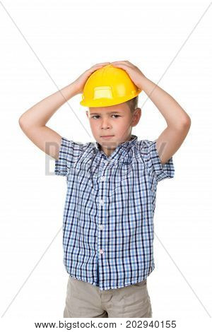 Adorable serious future builder in yellow helmet and blue checkred shirt, putting his hands on his head, isolated on white background.