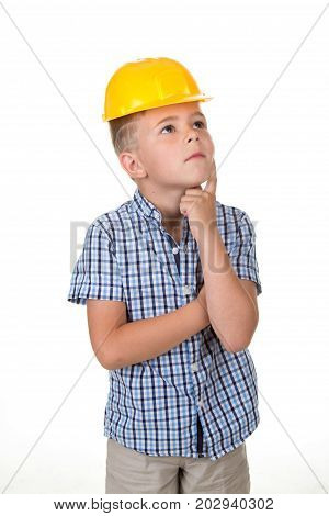 Adorable serious future builder in yellow helmet and blue checkred shirt, has a good idea, isolated on white background.