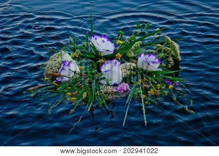 One beautiful large bouquet of a wreath of fresh wildflowers and green grass floating along the Ukrainian river of the Dnieper along the waves of water ripples on the feast of Ivan Kupala