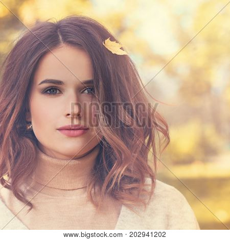 Beautiful Autumn Model Woman with Curly Bob Hairdo and Fall Maple Leaf Outdoors