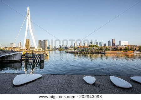 Landscape view on the riverside with beautiful buildings and modern bridge during the morning in Rotterdam city