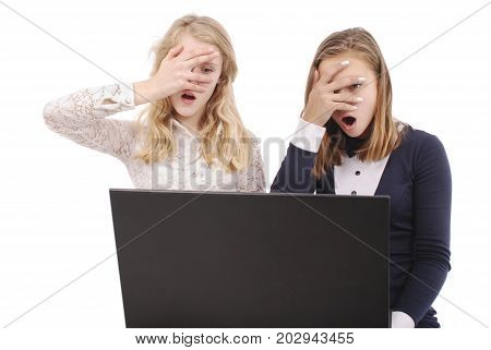 Two shocked girls using laptop isolated on a white background