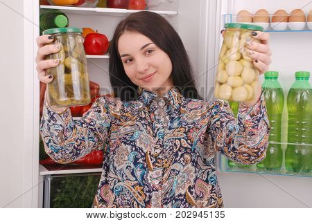 Young girl hold canned champignons and cucumbers on the refrigerator background