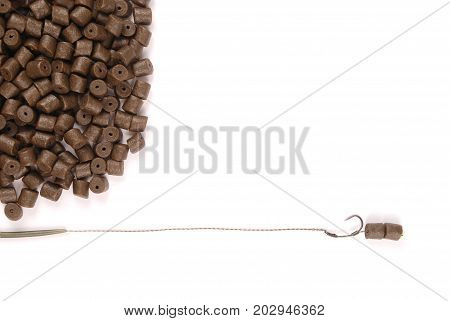 Fishing bait with hook and brown pre-drilled halibut pellets for carp fishing isolated on white background with soft shadow