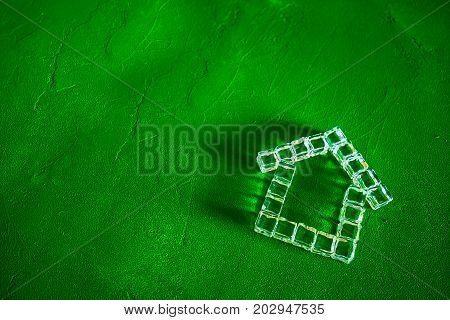 House made of ice cubes on a green background, the concept of real estate and ecology