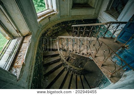 Top view of a rusty decorated staircase in abandoned mansion