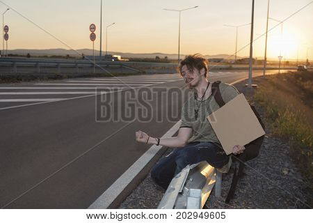 Young man sitting on a guardrail hitchhiking