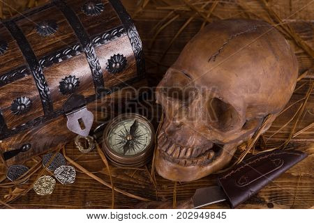 Human skull with treasure chest compass knife and coins