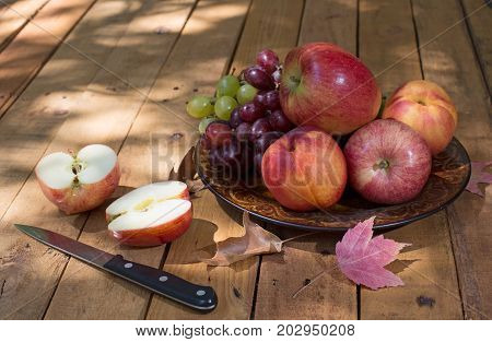 Plate of apples peaches and grapes with a sliced apple on a wooden surface