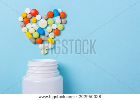 Assorted pharmaceutical medicine pills tablets and capsules for the treatment of heart disease. Heart shape and bottle of pills. Copy space for text