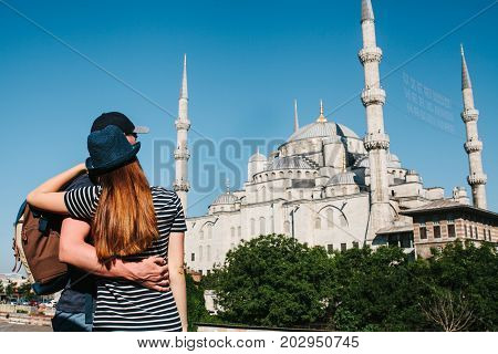 A couple of tourists a young man and a pretty woman embrace and look together at the world-famous Blue Mosque also called Sultanahmet in Istanbul, Turkey.