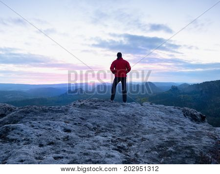 Man Silhouette On Cliff. Hiker In Red Jacket Climbed Up To Peak Enjoy View. Man  Watch Over Valley